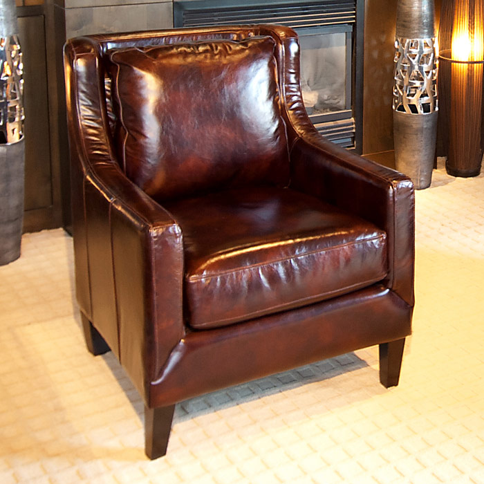 A Glass And Gold Bar Cart Brown Leather Armchair And